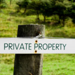 A fencepost sign to keep trespassers out. trespass, private, sign, farm, agriculture, property, field, word, fence, legal, ownership, land, horizontal, full frame, white, warning, run down, concept, rusty