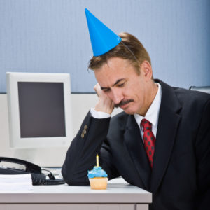Businessman looking at birthday cupcake