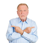 Closeup portrait of senior confused mature man, pointing two different directions, not sure which way to go in life, isolated white background. Negative emotions, facial expressions, feelings, dilemma